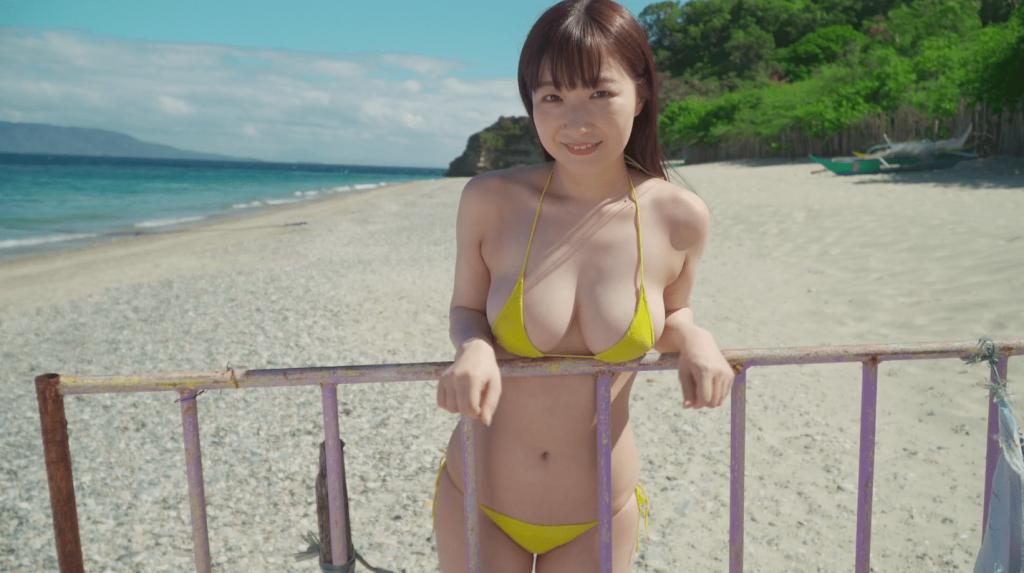 ビーチで黄色のビキニ姿で鉄柵の前に立つ小日向ななせ