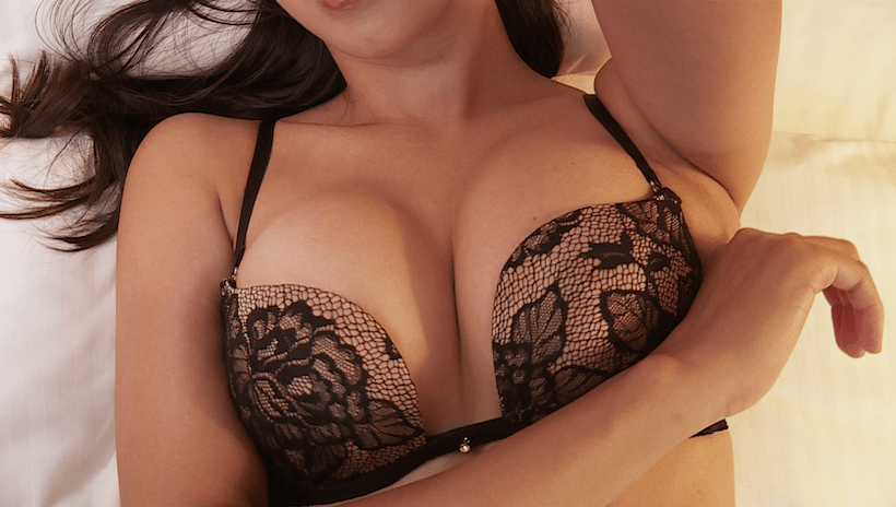 ベッドの上で黒の下着をつけている澤山璃奈のバスト