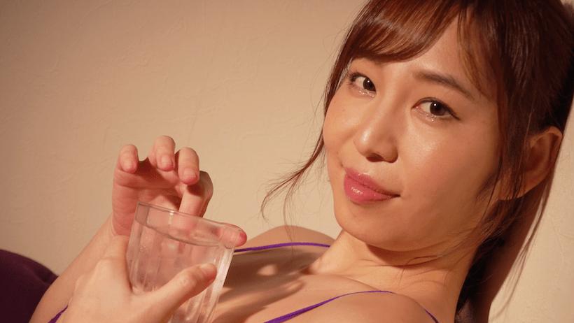 グラスの飲み物を指でかき混ぜる塩地美澄